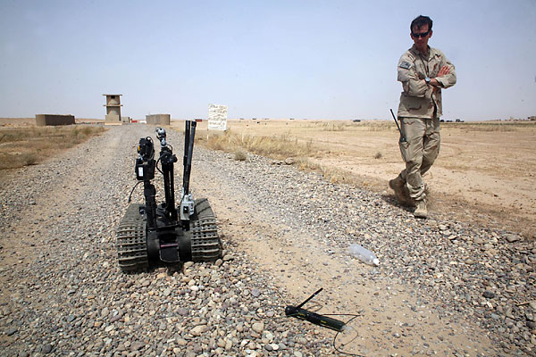 LT. j.g. Bruce Batteson, 31, looks over a Talon 4 robot during a training exercise at Camp Speicher on Aug. 6, 2010, in Iraq. He is part of the Navy's Explosive Ordnance Disposal Mobile Unit 2. (Ross Taylor | The Virginian-Pilot)