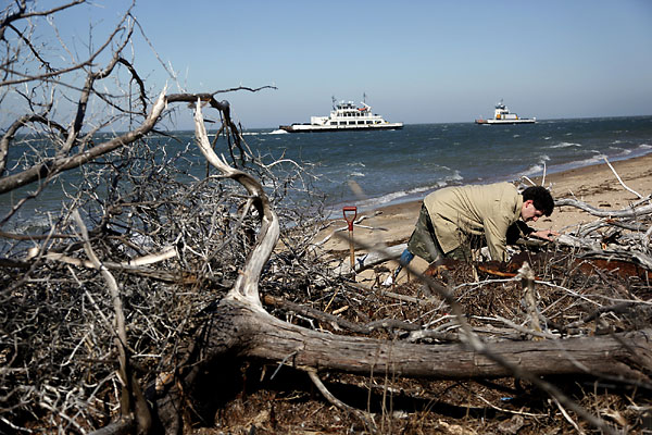 Matthew Farkas examines part of ship on Monday, Feb. 14, 2011, that he and Scott Dawson found on Hatteras Island on the Outer Banks, N.C.