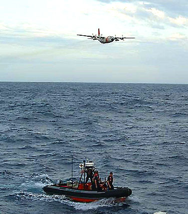 A C-130 airplane and a Coast Guard boat search for survivors of the sailing yacht Flying Colours.